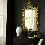 Decorating with mirrors - black wall and gold ornate mirror
