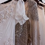 Beaded and detailed frocks hanging on rack - lace, white, silver