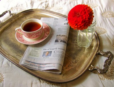 Romantic breakfast tray with tea, newspaper and flower