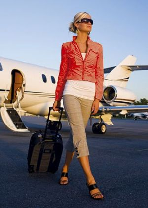 Woman traveller getting off jet with suitcase.jpg