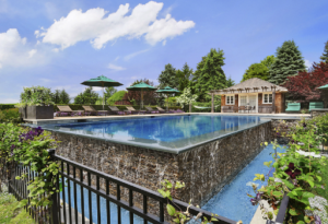 Shingle style pool house with pool and stream.png