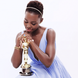Lupita Nyongo - stunning in her blue Prada dress and Oscar statuette.png