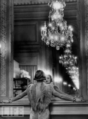 Model staring at herself in mirror with chandelier.jpg