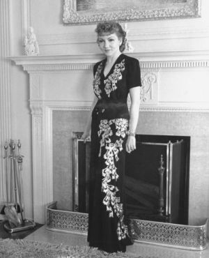 Claudette Colbert poses in front of the fireplace in her home in Holmby Hills 1939