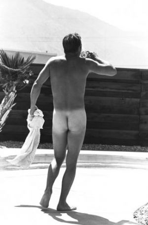 In 1963, McQueen strolls around his Hollywood backyard in the buff