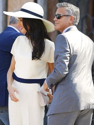 Amal in cream short-sleeved jacket with palazzo pants and a matching wide-brimmed hat.jpg