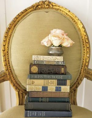 a pile of books on a gilt chair - Living lusciously.jpg