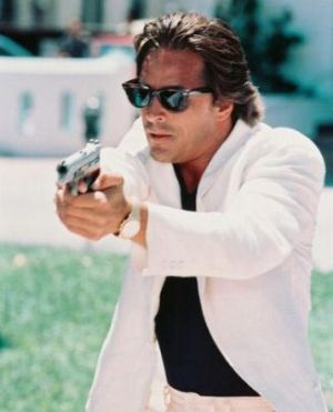 TV show fashion history - Miami Vice - Don Johnson with gun in white suit.jpg