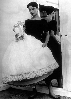 Audrey Hepburn in black frock carrying white frock.JPG